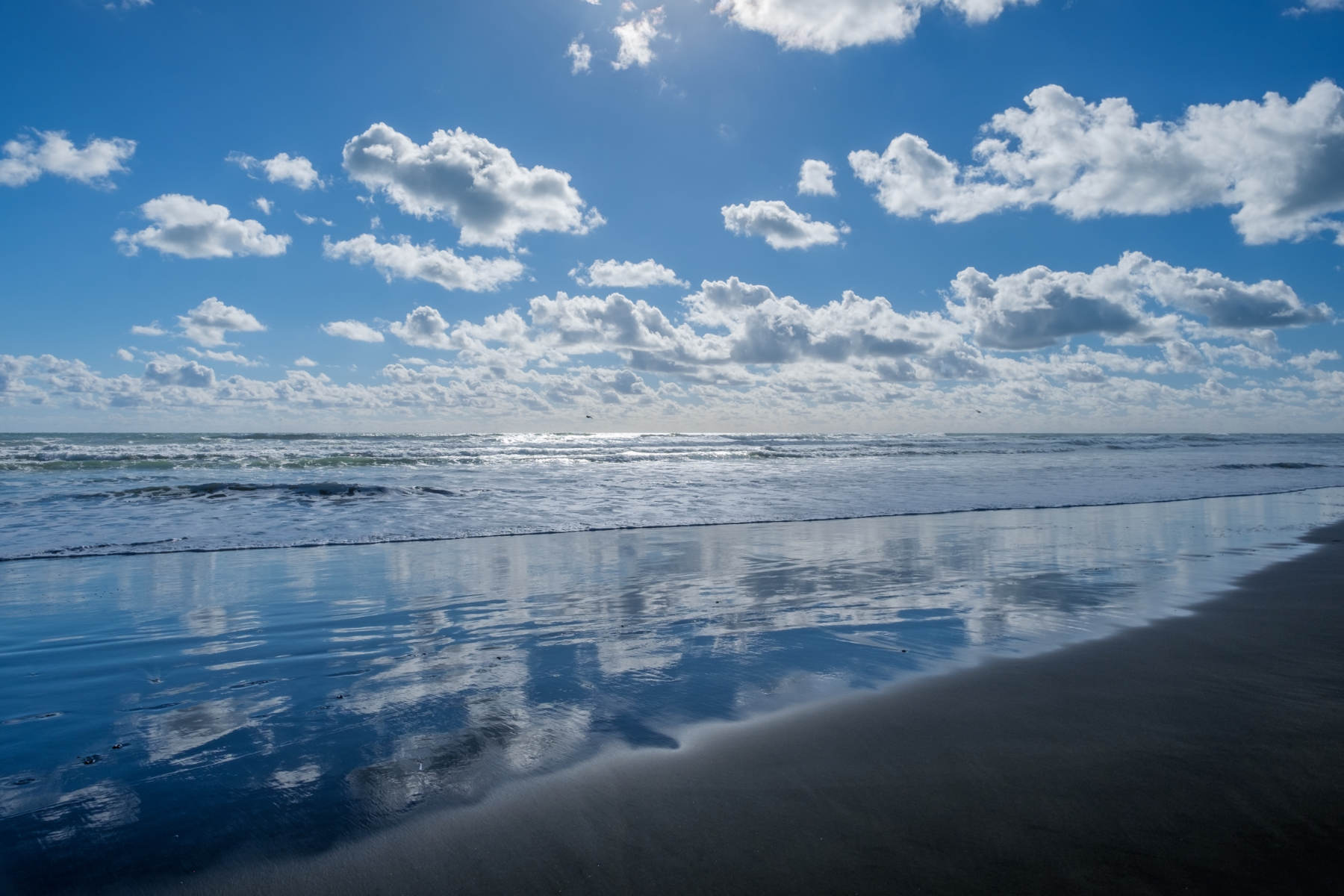 Piha beach clouds and reflections new zealand