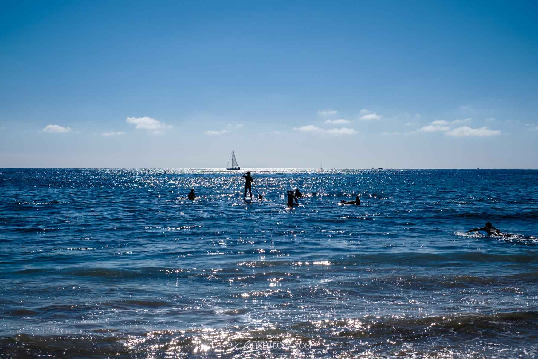 Sailboat and Silhouettes of people swimming
